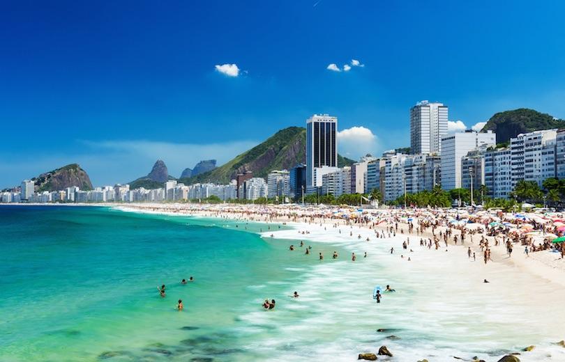 Copacabana: Separado de Ipanema al oeste por la playa Arpoador, Copacabana tiene un ambiente más activo que su famoso vecino . Los locales de Río , llamados cariocas, siempre parecen tener un partido de fútbol o voleibol en esta playa, y los vendedores a gritos venden sus bebidas y aperitivos en los quioscos que bordean la playa. El fuerte de Copacabana, una base militar con un museo de guerra que está abierto al público, se encuentra en un extremo de la playa. En la longitud de la playa al frente de la fortaleza , los pescadores ofrecen su captura por la mañana.Los visitantes y los cariocas les encanta pasear por el paseo marítimo que bordea los 4 km  de la playa larga. Originalmente construido en la década de 1930 , la pasarela cuenta con un diseño ondulado trazado en piedras blancas y negras.