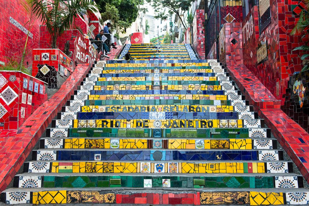 """Barrio Lapa: Situado en la sección del centro de Río conocido como el """"Centro"""" , el barrio de Lapa fue una vez el distrito de luz roja de la ciudad. Hoy en día, la zona es conocida por su vibrante vida nocturna. Llena de bares de samba, la música y el baile se siente en la calle en las noches del fin de semana. La mayor parte de la arquitectura del barrio se remonta a la década de 1800. Es el lugar perfecto para reunirse con amigos y cariocas para degustar la cocina local y para tomar caipirinha, el cóctel nacional hecho con caña de azúcar y limón. La Escalera de Selarón, conecta los barrios tanto de la Lapa y Santa Teresa."""